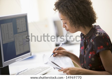 Woman in computer roon circling items in newspaper