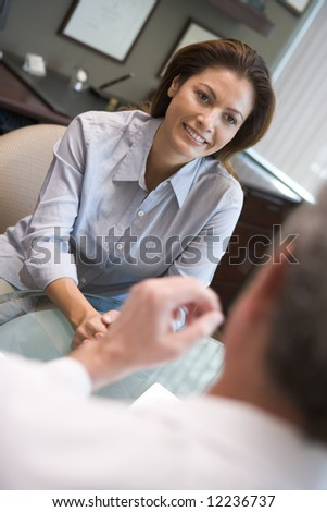Woman in consultation at IVF clinic talking to doctor - stock photo