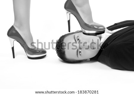 Woman in control of a man, sexy woman' foot on a man' face, dominating him and making him a slave - stock photo