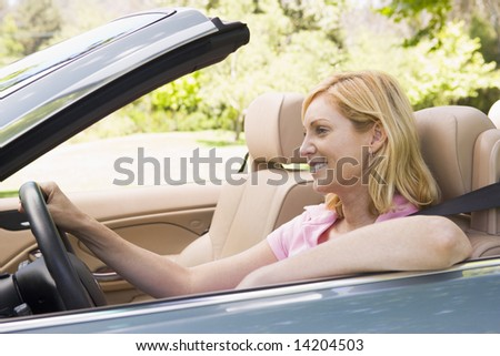 Woman in convertible car smiling - stock photo