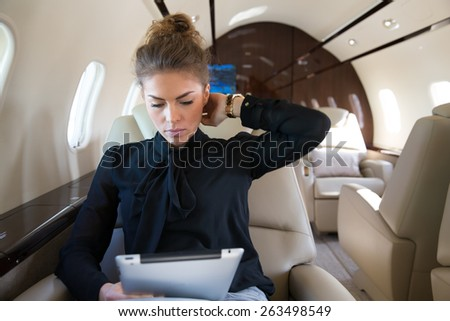 woman in corporate jet looking at tablet computer