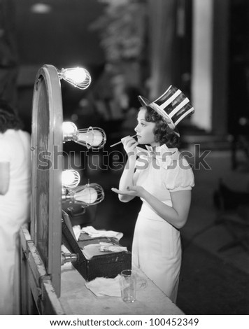 Woman in costume applying makeup - stock photo