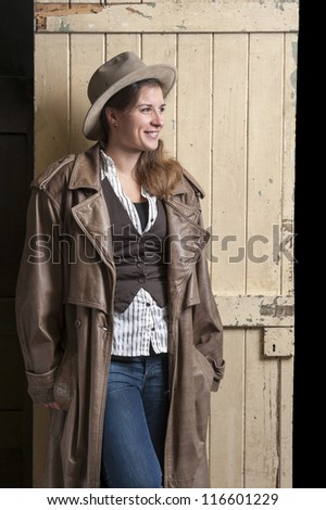 woman in cowboy coat and hat in an old barn - stock photo
