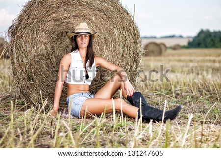 Woman in cowboy hat at field. - stock photo
