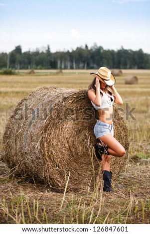 Woman in cowboy hat near a straw bale. - stock photo