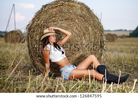 Woman in cowboy hat sitting near a straw bale. - stock photo