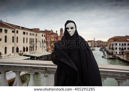 Woman in dark halloween like costume on streets of Venice during carnival - stock photo