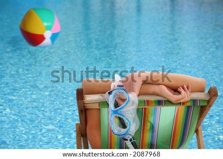 Woman in deckchair by blue pool with floating beachball