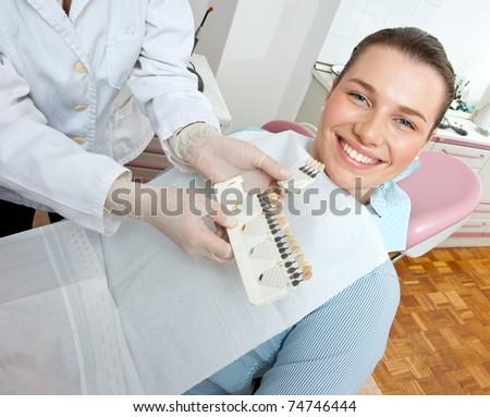 woman in dentist office choosing denture - stock photo