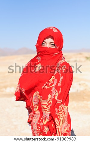 woman in desert in red shawl