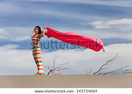 Woman  in desert with pink cloth. - stock photo