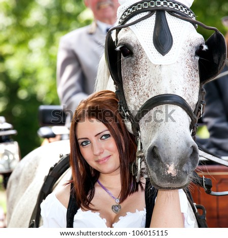Woman in dirndl with a horse and wedding carriage - stock photo