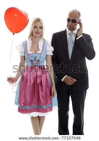 Woman in Dirndl with Bodyguard - stock photo