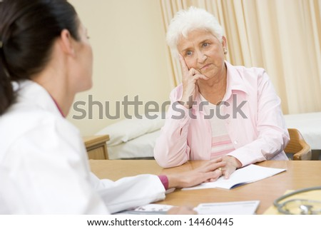Woman in doctor's office frowning - stock photo