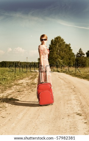 woman in   dress with  suitcase on road - stock photo