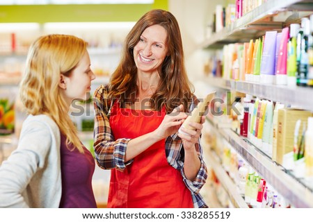 Woman in drugstore gets advice from saleswoman while shopping for cosmetics - stock photo