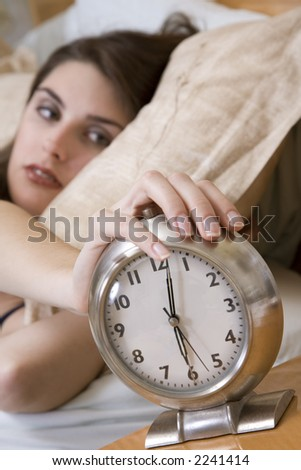Woman in early waking up to an alarm clock