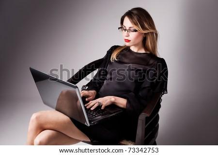 woman in elegant black dress with her laptop, studio shot - stock photo