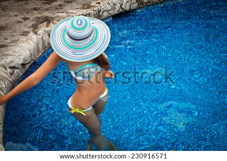 Woman in elegant straw hat standing in pool at tropical resort. Girl half in and half out of luxury pool water. Living the life of luxury - stock photo