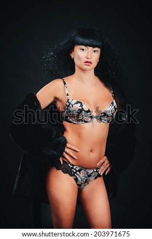 woman in erotic lingerie and a fur coat. Sexy woman with perfect body in the fur coat. - stock photo