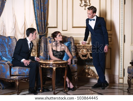 Woman in evening dress and young man in suit sitting in the armchairs and conversing with another man - stock photo