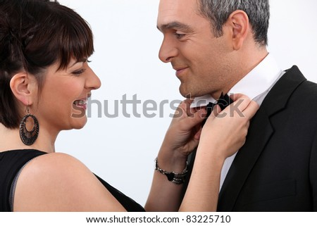 Woman in evening dress fixing her partner's bow tie - stock photo