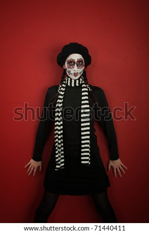 Woman in face paint leaning against a red wall - stock photo
