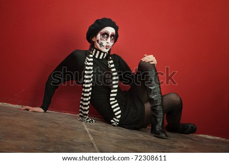 Woman in facepaint sits on the floor with her legs crossed - stock photo