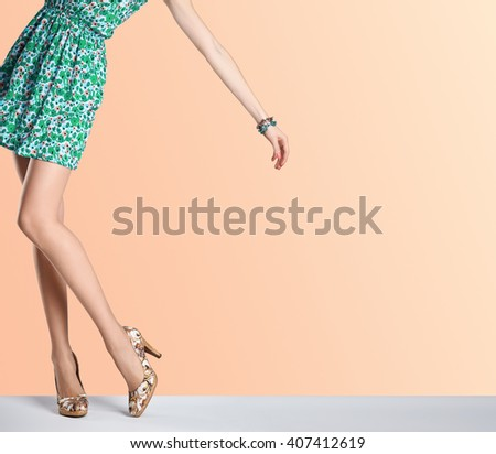Woman in fashion dress and high heels. Female sexy long legs, stylish green flower sundress and summer glamour shoes on orange. Unusual creative elegant walking out outfit, people.  Vintage,copy space - stock photo