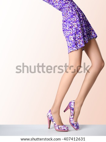 Woman in fashion dress and high heels. Female sexy long legs, stylish purple flower sundress and summer glamour shoes on pink. Unusual creative elegant walking out outfit, people.  Vintage, copy space - stock photo