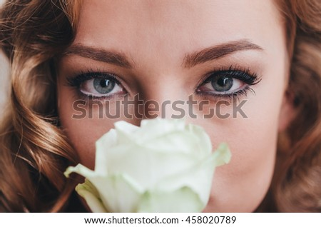 Woman in fashion red dress hold white rose in hands. Luxury indoor photo.