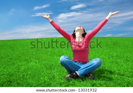 woman in field hold hand palm up under blue sky and clouds