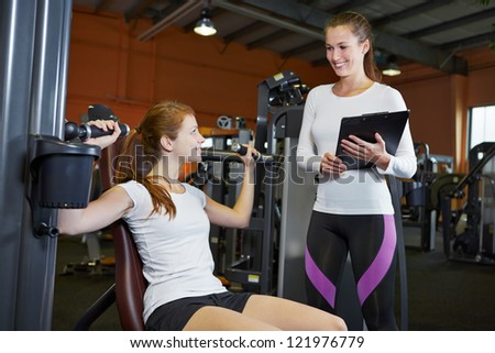 Woman in fitness center on a shoulder press listening to female trainer - stock photo