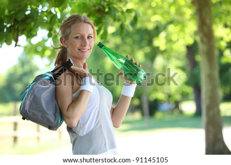 woman in fitness clothes drinking - stock photo