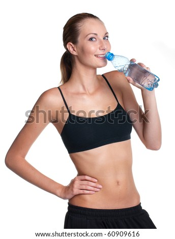 Woman in fitness pose holding water bottle - stock photo