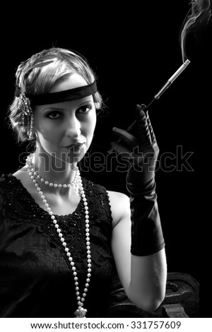 Woman in flapper dress in twenties style smoking a cigarette - stock photo