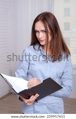 Woman in formal attire opened the folder for documents - stock photo