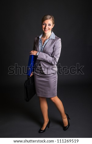 Woman in formal dress on dark gray background - stock photo