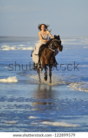 woman in formal dress riding horse in the ocean - stock photo