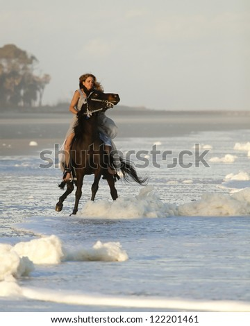 woman in formal dress riding wild horse on beach - stock photo