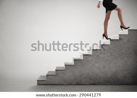 woman in formal wear walking up stairs over light grey background - stock photo