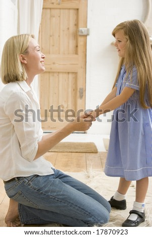 Woman in front hallway holding young girl's hands and smiling - stock photo
