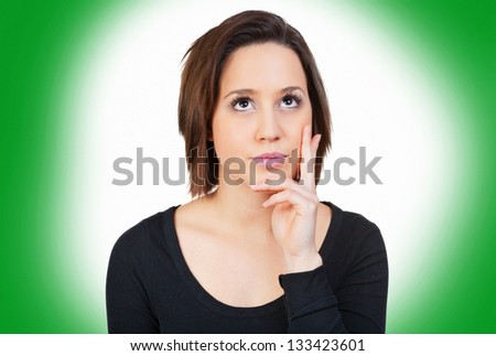 Woman in front of a green background is thinking - stock photo