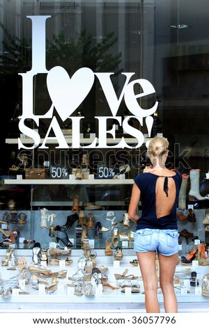 Woman in front of a shop Window With Sale Banners. Shopping Series. - stock photo