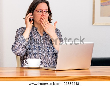 Woman in front of laptop is shocked by email - stock photo