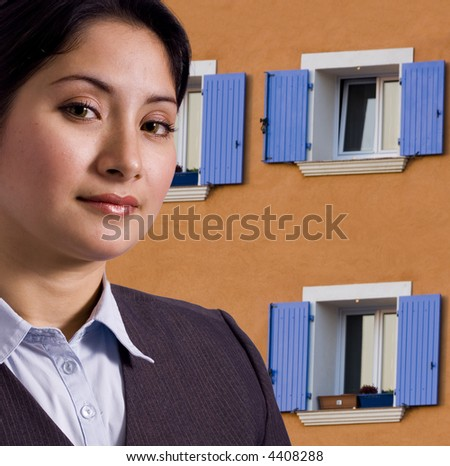 Woman in front of orange house with blue shutters