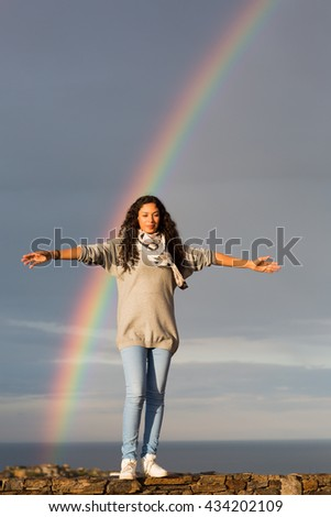Woman in front of rainbow with arms wide open - stock photo