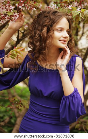 Woman in front of sakura spring blossoms - stock photo
