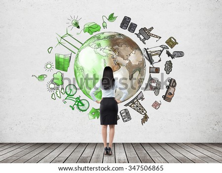 woman in front of the wall thinking about oil production and pollution, brown illustration of oil industry and green eco energy on white wall arranged in circle, concept of environment, back view - stock photo