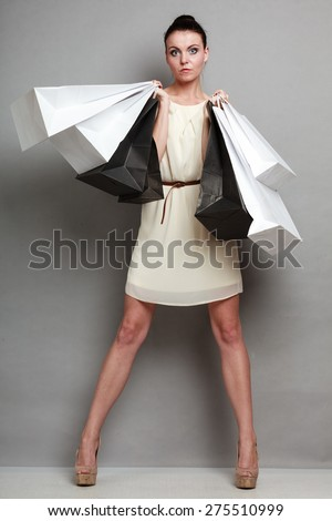 Woman in full length sale and retail concept. Elegant girl with black and white shopping bags in hands on grey background studio shot. - stock photo